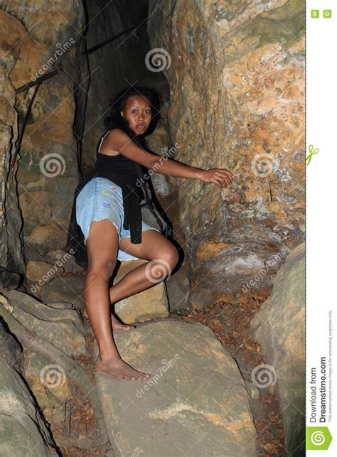 Girl climbing into cave stock image